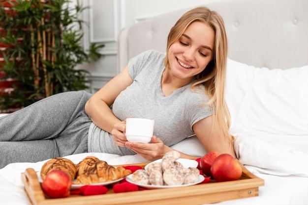 Średnio strzał kobieta w łóżku ze śniadaniem