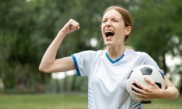 Średnio strzał kobieta z piłką wiwatuje