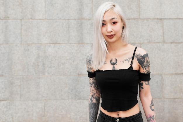 Średnio strzał kobieta z tatuażami pozuje