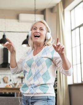 Średnio strzał kobieta zabawy ze słuchawkami na