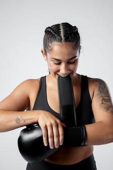 Średnio strzał kobieta zakłada rękawice bokserskie