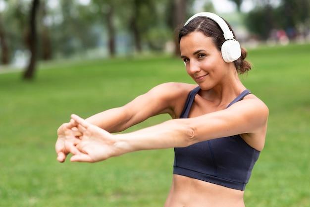 Średnio strzał kobieta ze słuchawkami rozciąganie ramion