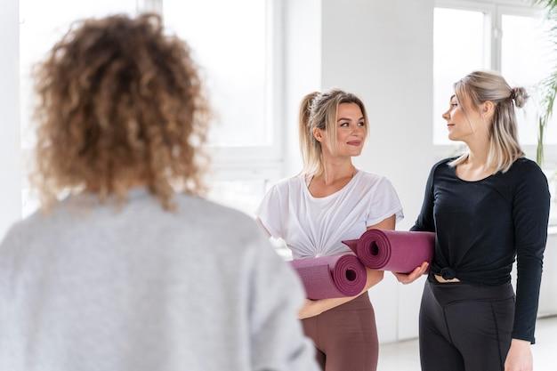 Średnio strzał kobiety trzymającej maty do jogi