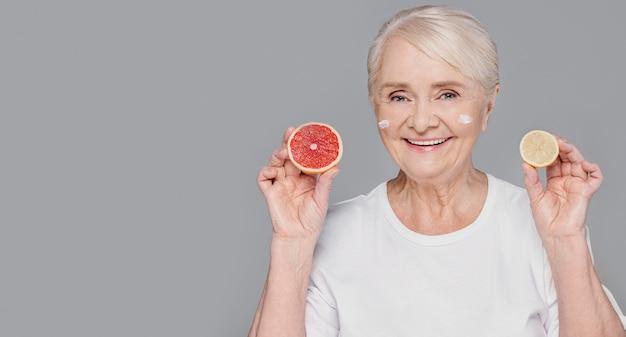 Średnio strzał kobiety trzymającej owoce cytrusowe