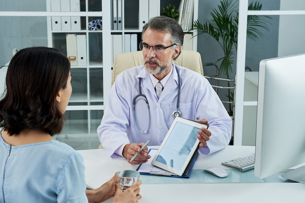 Średnio strzał lekarza w średnim wieku wyjaśniającego diagnozę za pomocą komputera typu tablet