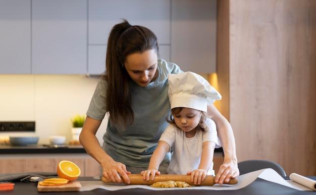 Średnio strzał matka i dziecko za pomocą wałka do ciasta