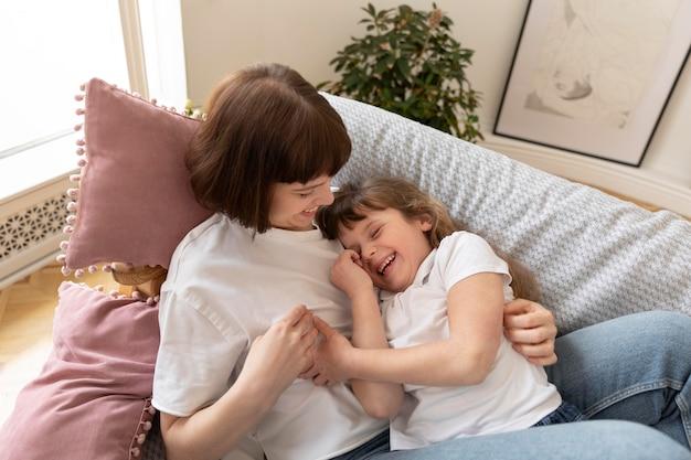 Średnio strzał matka i dziewczyna leżące na kanapie