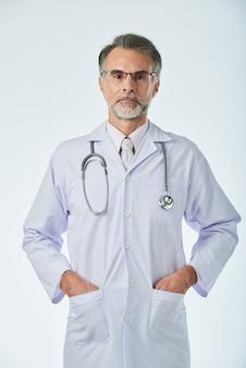 Średnio strzał medycznego specjalisty pozyci z rękami w kieszeniach patrzeje kamerę