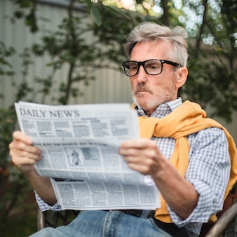 Średnio strzał mężczyzna czyta gazetę