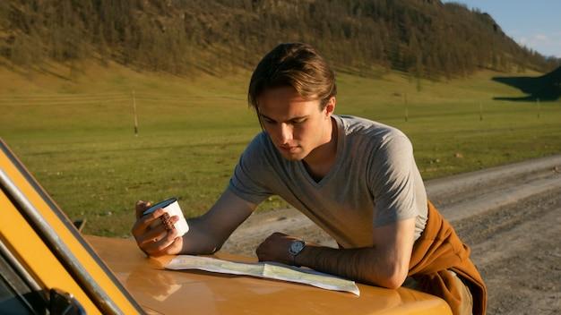Średnio strzał mężczyzna czytający mapę na zewnątrz