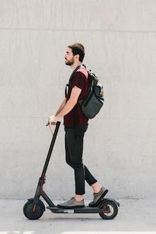 Średnio strzał mężczyzna jedzie na e-hulajnodze na ulicy