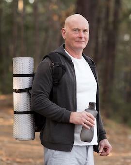 Średnio strzał mężczyzna niosący matę do jogi