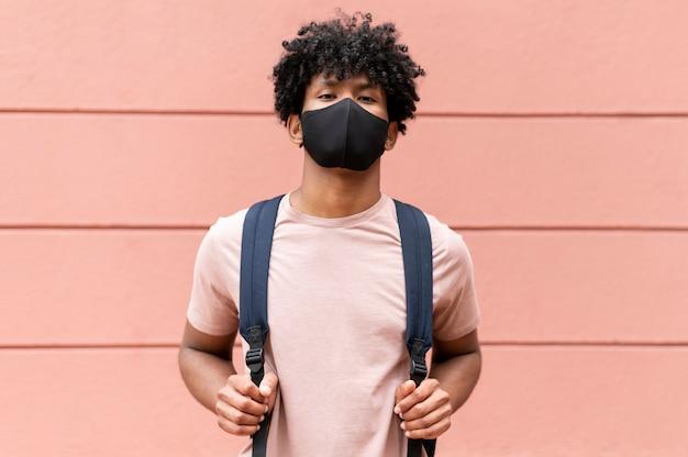 Średnio strzał mężczyzna noszący maskę na zewnątrz na zewnątrz