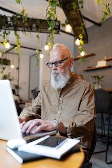 Średnio strzał mężczyzna piszący na laptopie