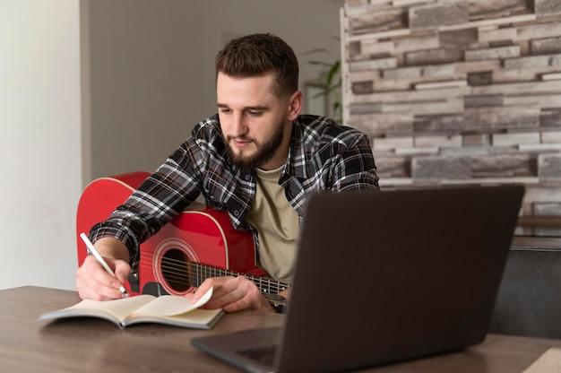 Średnio strzał mężczyzna pisze na notebooku