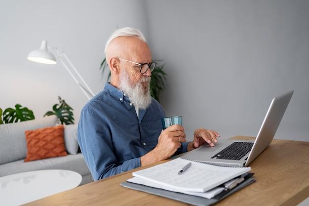 Średnio strzał mężczyzna studiujący przy biurku z laptopem