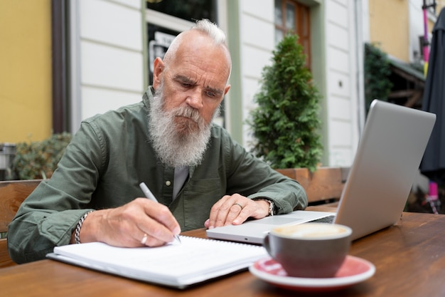 Średnio strzał mężczyzna studiujący z laptopem