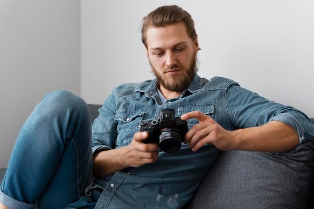 Średnio strzał mężczyzna trzyma aparat fotograficzny