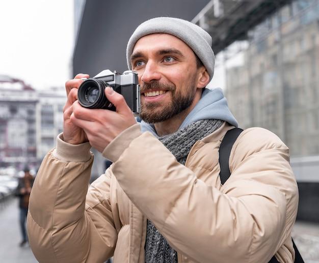 Średnio strzał mężczyzna trzyma aparat