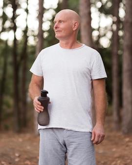 Średnio strzał mężczyzna trzyma butelkę wody