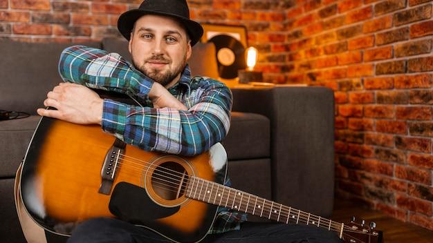 Średnio strzał mężczyzna trzyma gitarę