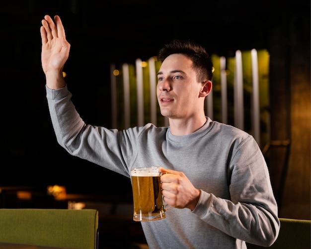 Średnio strzał mężczyzna trzyma kufel piwa