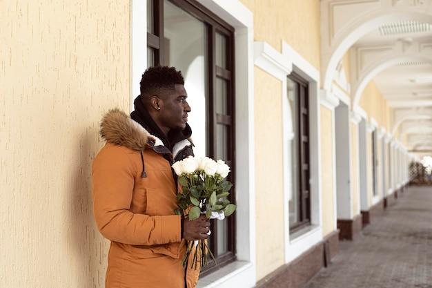Średnio strzał mężczyzna trzyma kwiaty