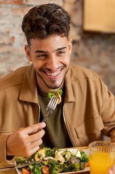 Średnio strzał mężczyzna trzyma widelec z jedzeniem