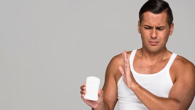 Średnio strzał mężczyzna trzymający dezodorant