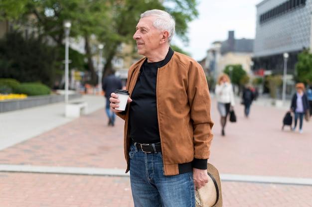 Średnio strzał mężczyzna trzymający filiżankę kawy