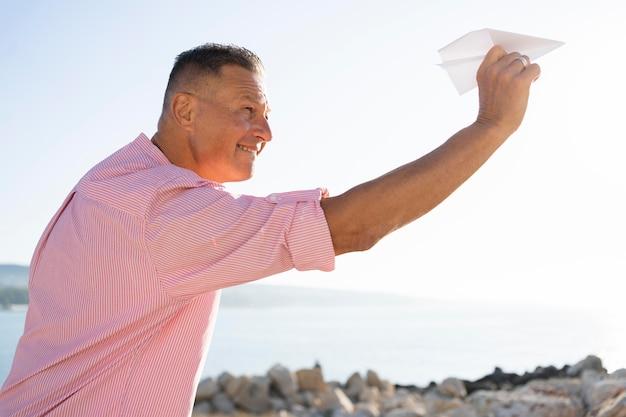 Średnio strzał mężczyzna trzymający papierowy samolot