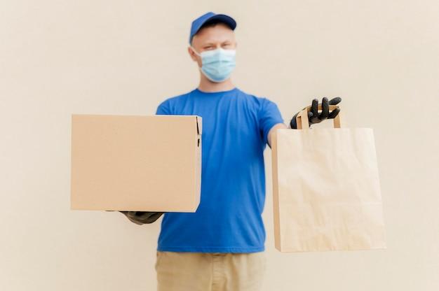 Średnio strzał mężczyzna trzymający pudełko i torbę