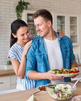 Średnio strzał mężczyzna trzymający talerz z jedzeniem