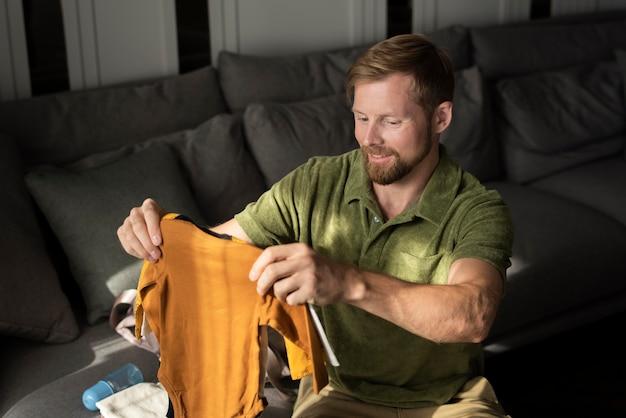 Średnio strzał mężczyzna trzymający ubrania dla dzieci