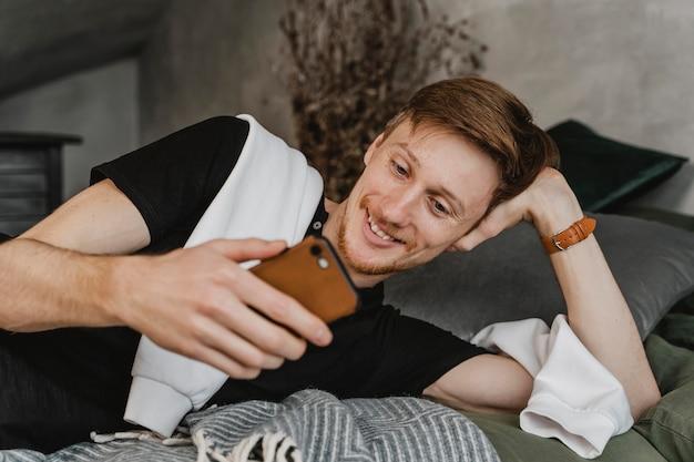 Średnio strzał mężczyzna uśmiecha się do smartfona