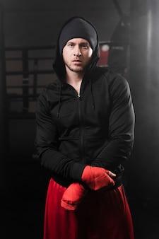 Średnio strzał mężczyzna w odzieży sportowej w centrum treningowym boksu