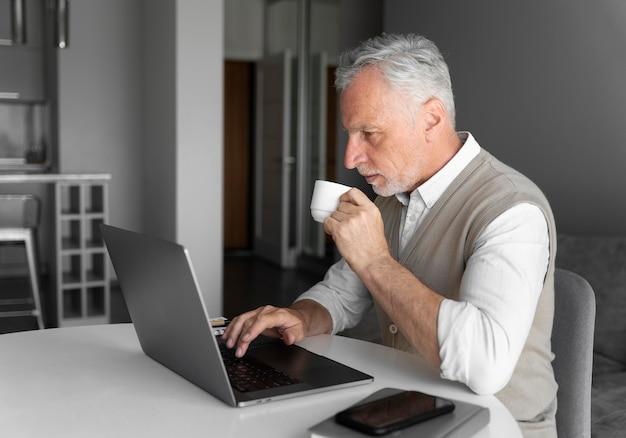 Średnio strzał mężczyzna z laptopem i kubkiem