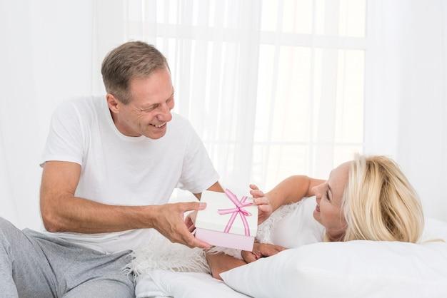 Średnio strzał mężczyzna zaskakująca kobieta z prezentem