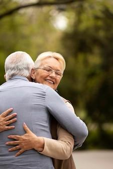 Średnio strzał mężczyzny i kobiety przytulających się na zewnątrz