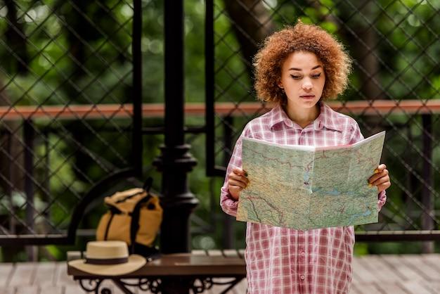 Średnio strzał młoda kobieta sprawdza mapę w poszukiwaniu nowego miejsca docelowego