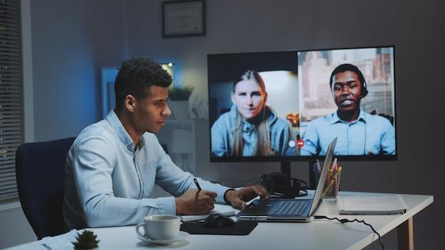 Średnio strzał młodego afrykańskiego dyrektora naczelnego podczas rozmowy wideo na dużym monitorze z kolegami poddanymi kwarantannie