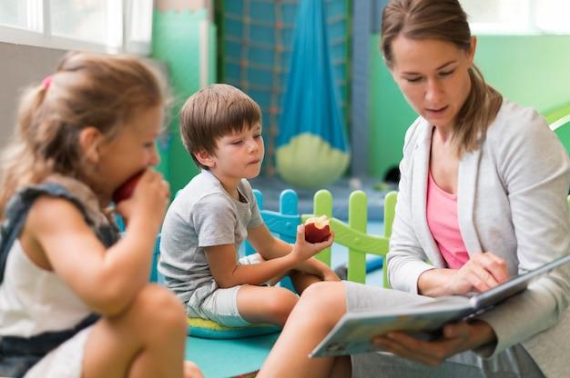 Średnio strzał nauczyciela czytającego dzieciom
