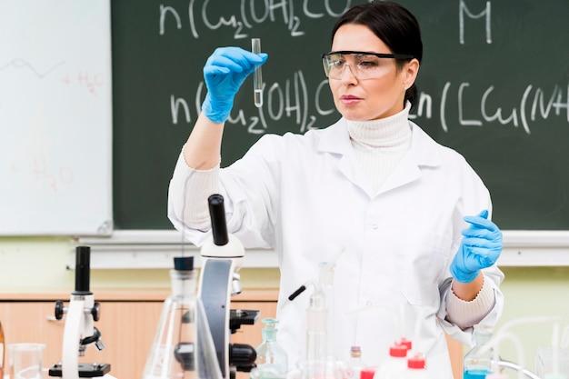 Średnio strzał naukowiec trzymając probówkę laboratoryjną
