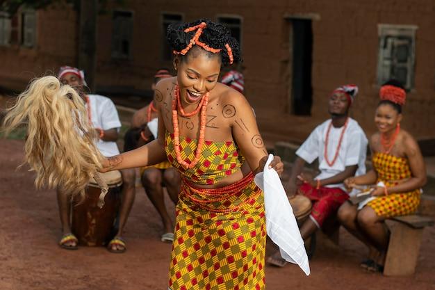 Średnio strzał nigeryjska kobieta tańczy na zewnątrz