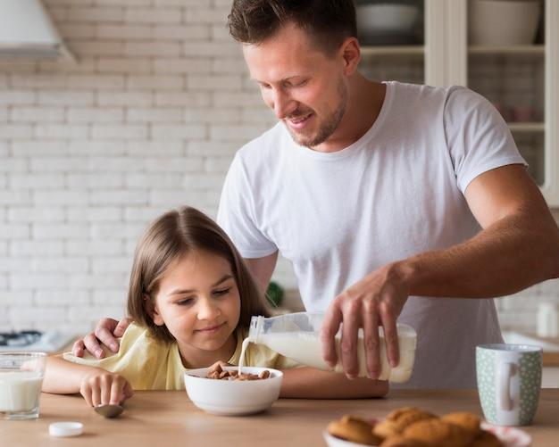 Średnio strzał ojca wlewającego mleko do miski