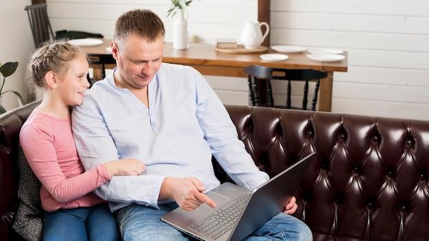 Średnio strzał ojciec i dziewczyna z laptopem