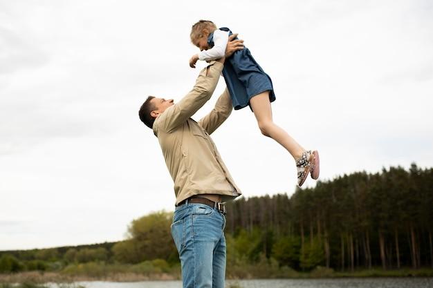 Średnio strzał ojciec trzymający dziecko w górze