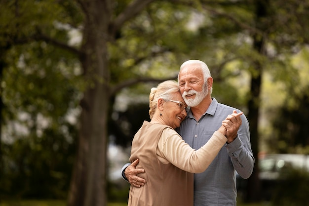 Średnio strzał para starszych tańczących na zewnątrz
