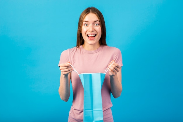 Średnio strzał portret szczęśliwej kobiety trzymającej torbę na zakupy