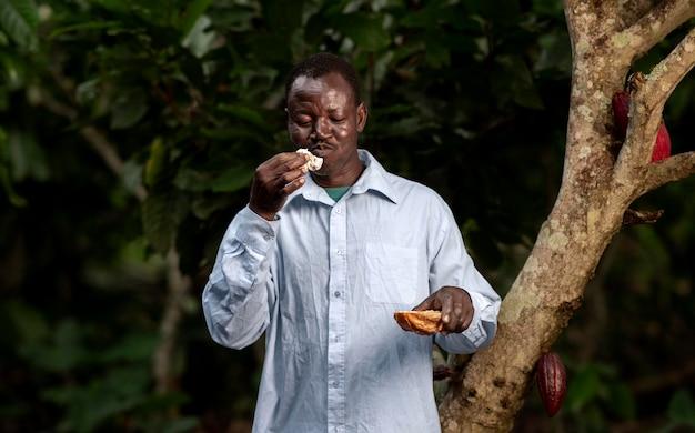 Średnio strzał rolnik jedzący na zewnątrz